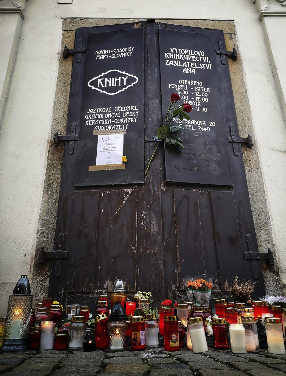 Candles and flowers are placed in front of Jaromir Vytopil's bookstore in Pelhrimov, Czech Republic, Wednesday, Nov. 11, 2020. Some 25,000 have been killed by COVID-19 in the hard-hit Czech Republic. Jaromir Vytopil was one of them. His everyday presence in the small Czech town of Pelhrimov was something everybody took for granted for seven decades as he had served the generations of readers. The longest serving Czech bookseller, passed away on Nov 9. 2020, at age of 83. (AP Photo/Jan Vytopil)