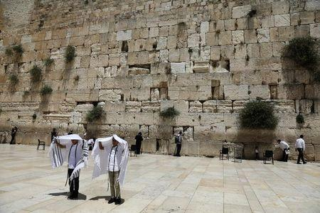 FILE PHOTO: Youth hold their prayer shawls as they stand in front of the Western Wall, Judaism's holiest prayers site in Jerusalem's Old City