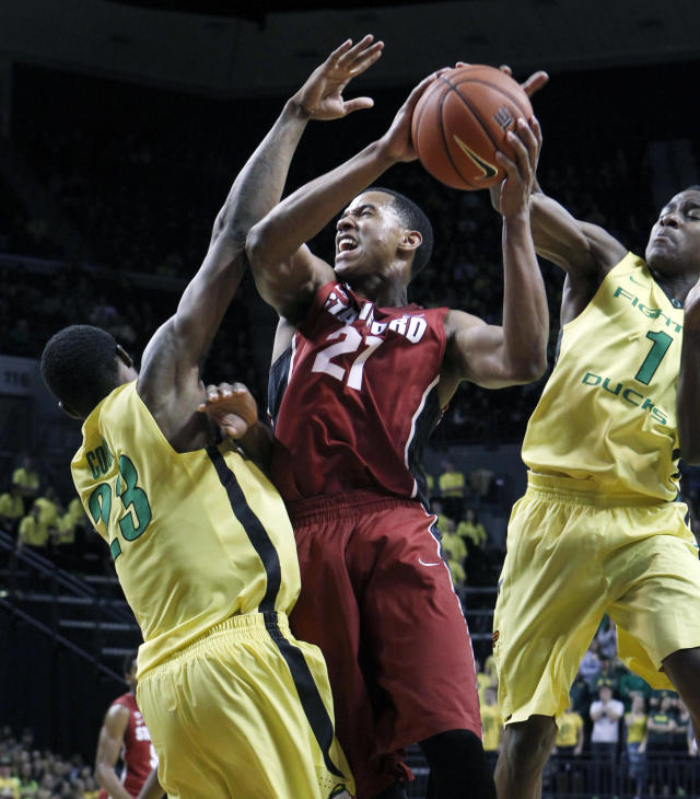 Stanford's Anthony Brown, center, drives through Oregon's Elgin Cook, left, and Dominic Artis, right, during the first half of an NCAA college basketball game Eugene, Ore. on Sunday, Jan. 12, 2014. (AP Photo/ Chris Pietsch)
