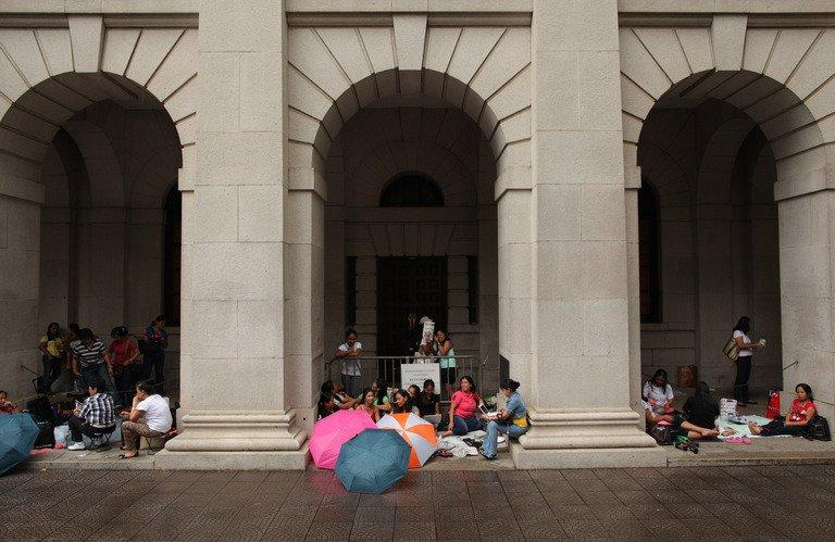 Foreign domestic helpers sit beneath the arches of the former Legislative Council building in Hong Kong