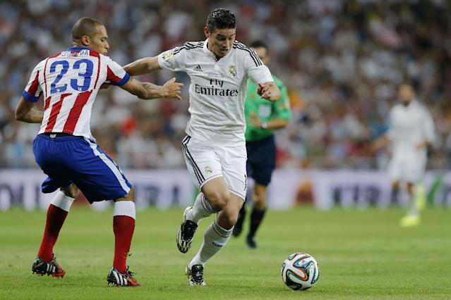 Real Madrid's James Rodriguez from Colombia, fights for the ball with Atletico Madrid's Joao Miranda from Brazil, left, during a Spanish Super Cup soccer match at Santiago Bernabeu stadium in Madrid, Spain, Tuesday, Aug. 19, 2014 . (AP Photo/Daniel Ochoa de Olza)