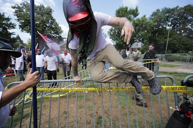 "<p>White nationalists, neo-Nazis and members of the ""alt-right"" leap over barricades inside Lee Park during the ""Unite the Right"" rally Aug. 12, 2017 in Charlottesville, Va. (Photo: Chip Somodevilla/Getty Images) </p>"