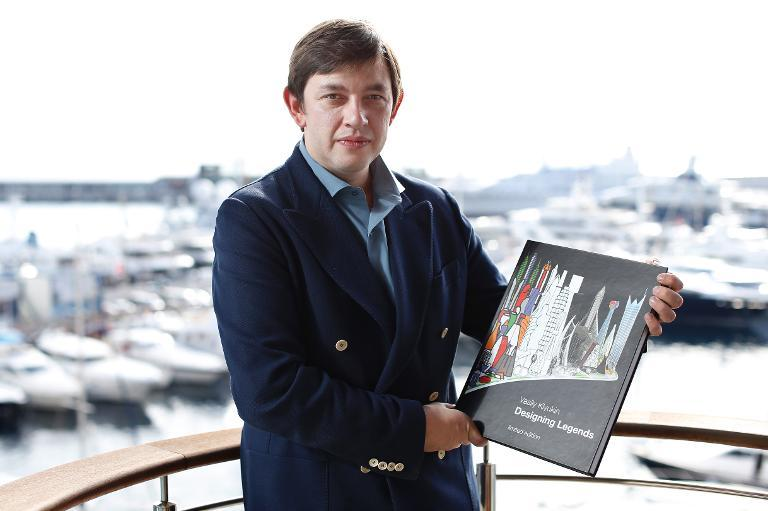 Russian millionaire Vasily Klyukin poses for a photo at home, with his book, in Monaco, on October 25, 2013