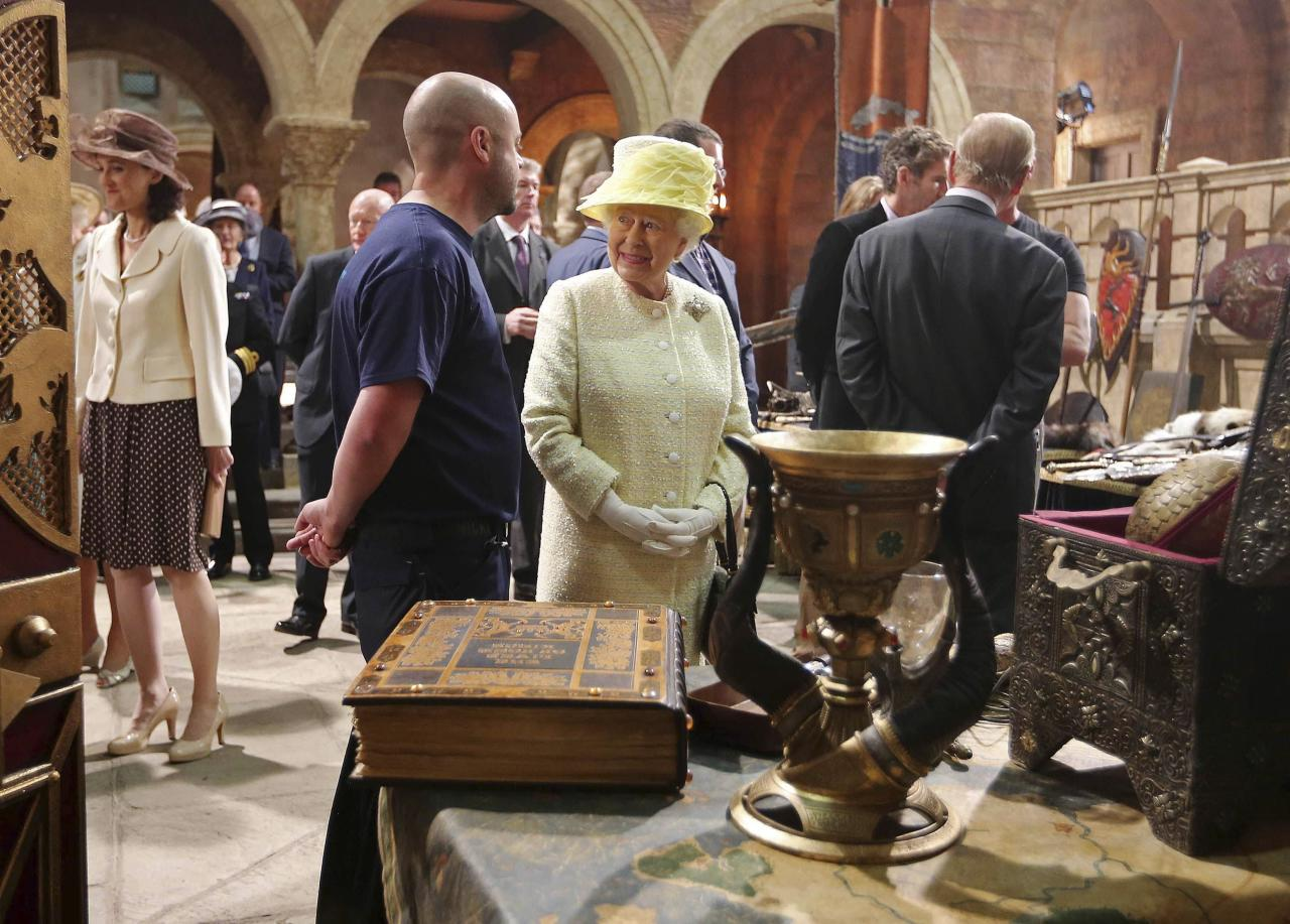 Britain's Queen Elizabeth talks to an unidentified guest as she looks at props during her visit to the set of the television series Game of Thrones, in the Titanic Quarter of Belfast, Northern Ireland, June 24, 2014. REUTERS/Jonathan Porter/Pool (NORTHERN IRELAND - Tags: ROYALS ENTERTAINMENT SOCIETY)