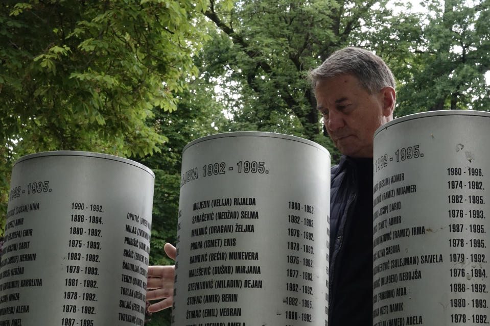 Fikret Grabovica who lost his 11-year-old daughter by Bosnian Serb shelling look at the names at the memorial for children killed during 1002-1995 siege, in Sarajevo, Bosnia, Monday, May 31, 2021. U.N. judges on Tuesday, June 8 deliver their final ruling on the conviction of former Bosnian Serb army chief Radko Mladic on charges of genocide, war crimes and crimes against humanity during Bosnia's 1992-95 ethnic carnage. Nearly three decades after the end of Europe's worst conflict since World War II that killed more than 100,000 people, a U.N. court is set to close the case of the Bosnian War's most notorious figure. (AP Photo/Eldar Emric)