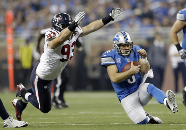 Detroit Lions quarterback Matthew Stafford (9) slides after scrambling away from Houston Texans defensive end Jared Crick (93) during the fourth quarter of an NFL football game at Ford Field in Detroit, Thursday, Nov. 22, 2012. (AP Photo/Paul Sancya)