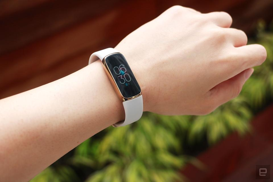 Slight off angle view of the Fitbit Luxe with a light pink silicone band on a wrist against a dark brown background with some greenery. The screen shows the time is 6:30pm.