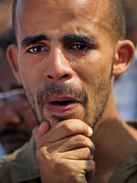 A Sudanese man weeps over the body of Salah Sanhory, 26, who was killed on Friday Sept. 27, 2013 by security forces, during his funeral in Khartoum, Sudan, Saturday, Sept. 28, 2013. The regime of President Omar al-Bashir is trying to stop public anger over fuel price hikes from turning into an Arab Spring-style uprising against his 24-year rule. But a crackdown by security forces appears to be fueling the unrest. (AP Photo/Khalil Hamra)