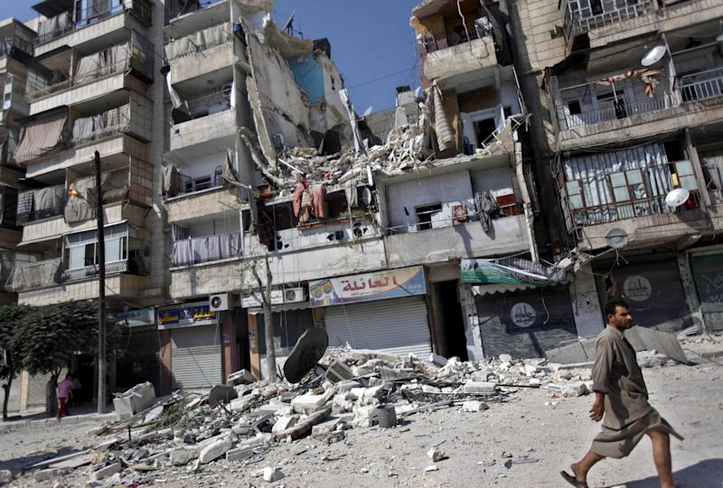 A Syrian man walks by a building destroyed in an airstrike in Aleppo city, Syria, Friday, Aug. 17, 2012. Rebel footholds in Aleppo have been the target of weeks of Syrian shelling and air attacks as part of wider offensives by President Bashar Assad's regime. Rebels have been driven from some areas, but the report of clashes near the airport suggests the battles could be shifting to new fronts. (AP Photo/Khalil Hamra)