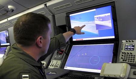 Still image from United States Navy video shows a U.S. Navy crewman aboard a surveillance aircraft viewing a computer screen purportedly showing Chinese construction on the reclaimed land of Fiery Cross Reef in the disputed Spratly Islands