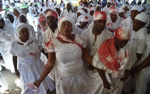 <span>A Haitian voodoo follower wearing white clothes is seen in trance while participate in a voodoo ceremony in Souvenance, a suburb of Gonaives, 171km north of Port-au-Prince, on April 1, 2018</span> <span>Credit: AFP </span>
