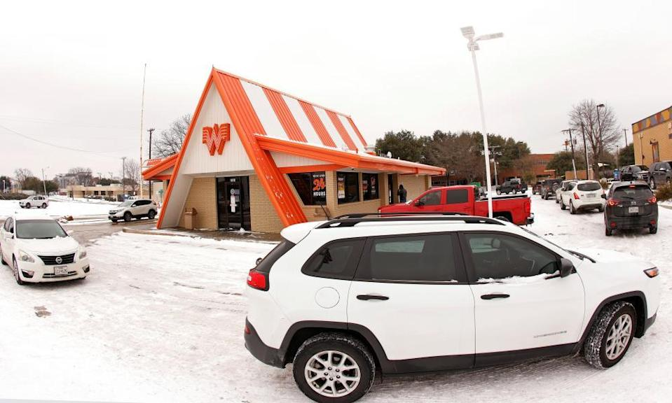 Cars wrap around a Whataburger franchise as they line up to order food after the storm.