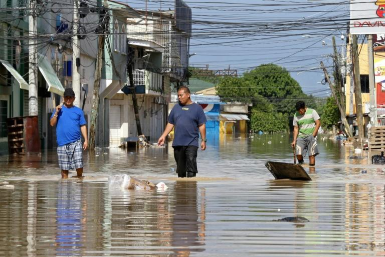Men wade through floodwaters left behind by Hurricane Iota in La Lima, near San Pedro Sula in Honduras