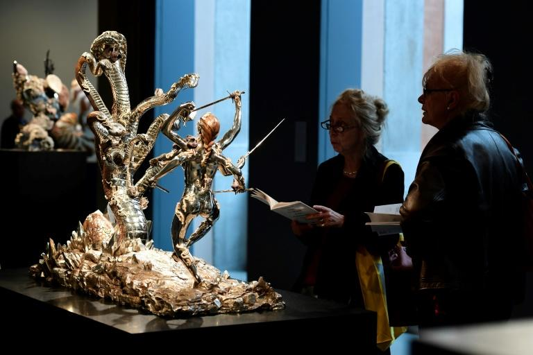 "People look at a silver sculture titled ""Hydra and Kali"" by British artist Damien Hirst during the press presentation of his exhibit ""Treasures from the Wreck of the Unbelievable"" at the Pinault Collection in Venice on April 6, 2017"