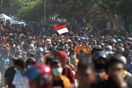 A protester raises the Indonesian flag while marching to the local parliament building during a protest in Kendari