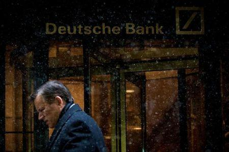 A man walks past the Deutsche Bank offices during a snow storm in Manhattan's financial district in New York