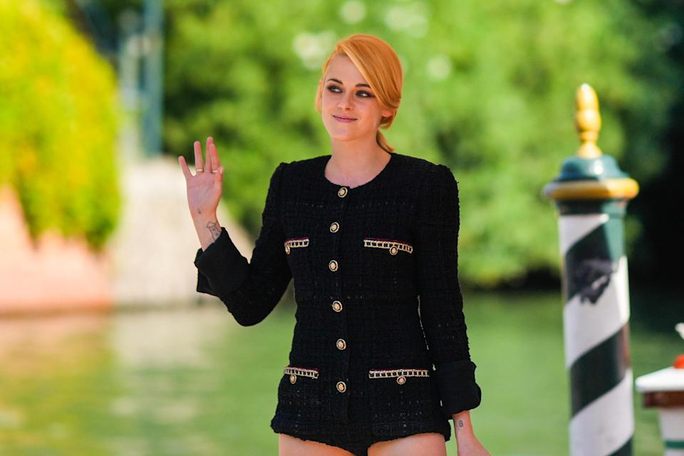 Kristen wears a long-sleeved tweed jacket top with large buttons and matching shorts as she waves to people at the Venice Film Festival