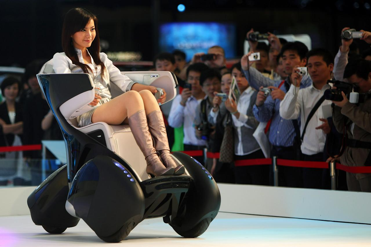 SHANGHAI, CHINA - APRIL 23:  A model drives a Toyota i-REAL concept car on display during a special trade visitors opening of the Auto Shanghai 2009 at Shanghai New International Expo Center on April 23, 2009 in Shanghai, China. More than 1,500 automakers and auto-parts manufacturers from 25 countries and regions will attend the auto show, which is scheduled to be held from April 20 to April 28. Driven by the government policies to stimulate car consumption, China's automobile sales rose 5 percent in March to a record high of 1.11 million vehicles, according to the China Association of Automobile Manufacturers.  (Photo by Feng Li/Getty Images)
