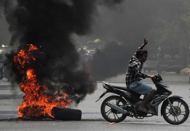 Man flashes three-finger salute next to burning tires during a protest against the military coup, in Mandalay