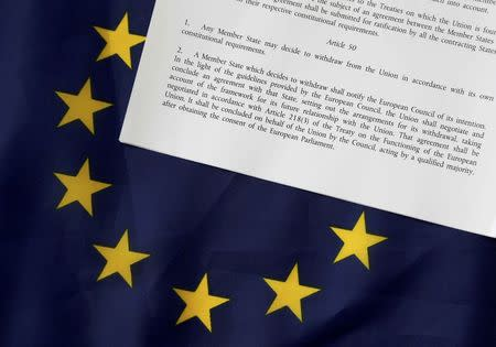 FILE PHOTO - Article 50 of the EU's Lisbon Treaty that deals with the mechanism for departure is pictured with an EU flag following Britain's referendum results to leave the European Union, in this photo illustration taken in Brussels, Belgium, June 24, 2016. REUTERS/Francois Lenoir/Illustration/File Photo