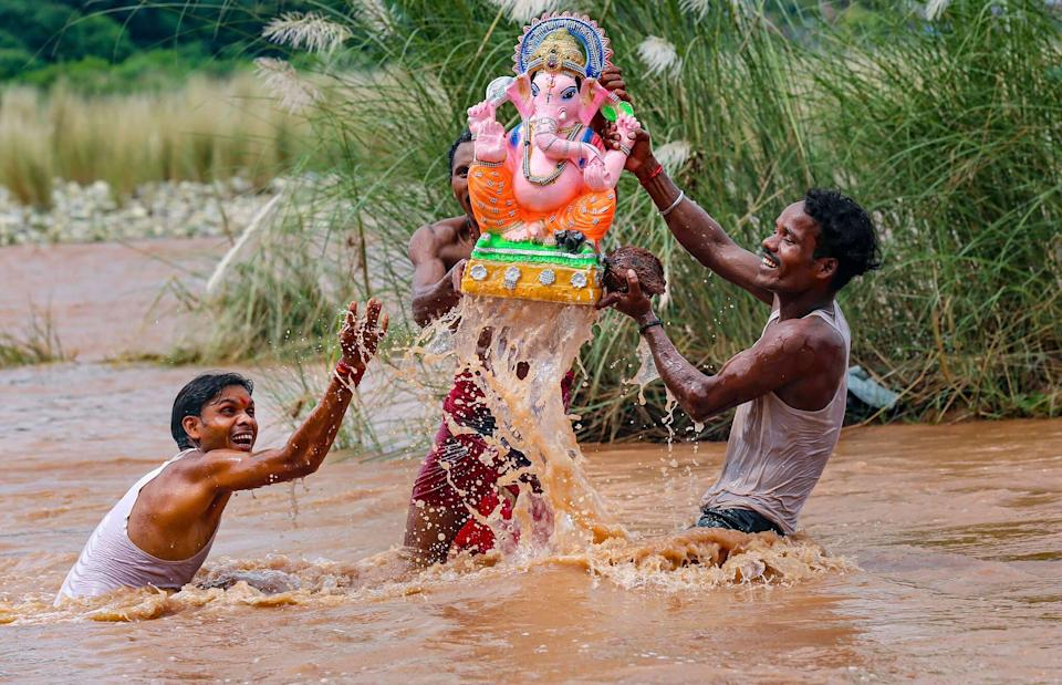 Devotees carry an idol of Lord Ganesh for immersion in the Tawi river, in Jammu, on Friday. (PTI Photo)