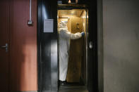 In this image released by World Press Photo, Thursday April 15, 2021, by Laurence Geai, part of a series titled Pandemic in France, which won the third prize in the General News Stories category, shows A morgue employee transports a coffin from the fifth floor of an apartment block, in the Parisian suburb of Pantin, on April 23, 2020. (Laurence Geai, World Press Photo via AP)