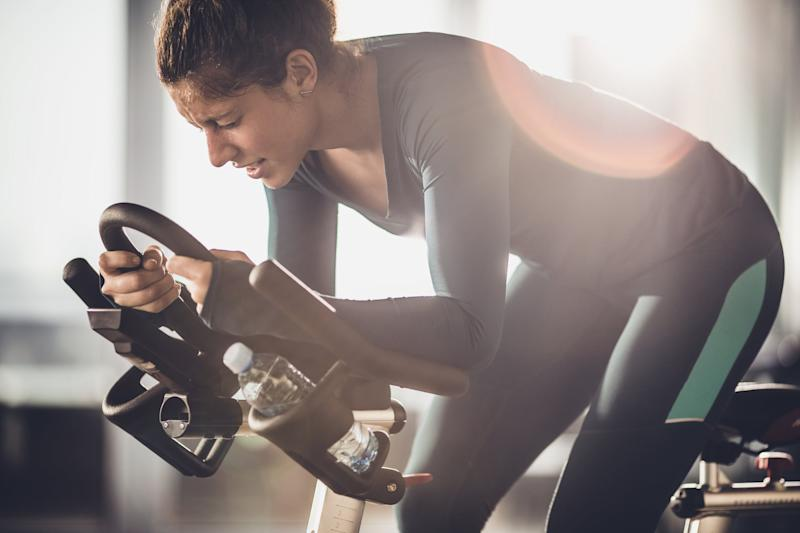 Determined female athlete making an effort on a exercising class in a health club.