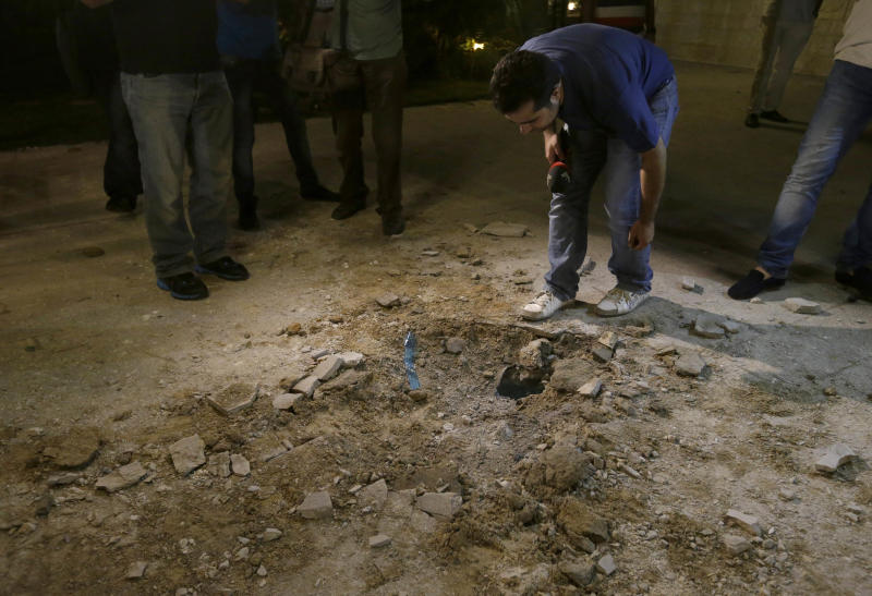 A Lebanese journalist looks at a small crater left by a rocket attack, at a villa few meters away from one of the entrances to the Lebanese presidential palace, in Fayadiyyeh area, eastern Beirut, Lebanon, early Friday, Aug. 2, 2013. At least two rockets slammed Thursday night into an area south of the Lebanese capital that houses the Defense Ministry and presidential palace, Lebanon's state-run news agency said. The attack comes on the same day when President Michel Suleiman gave a speech on the occasion of Army Day in which he criticized the involvement of the militant Lebanese Hezbollah group in the Syrian civil war in support of Assad's forces. (AP Photo/Hussein Malla)