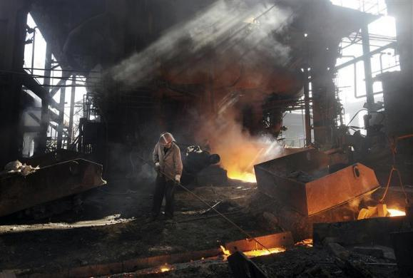 A laborer works at a steel and iron factory in Hefei, Anhui province November 22, 2009.