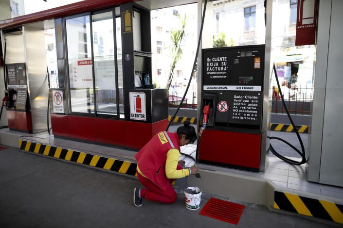 A woman paints a closed gas station in La Paz, Bolivia, Monday, Nov. 18, 2019. The blockades of former president Evo Morales' supporters on the outskirts of the main cities of Bolivia are causing a shortage of gasoline and food, which puts pressure on the interim government that seeks to open a dialogue to end four weeks of social and political upheaval. (AP Photo/Natacha Pisarenko)