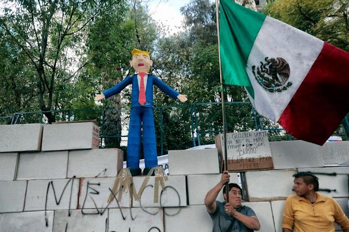 People protest against US President Donald Trump's inauguration next to a fake wall with a Mexican national flag and a dummy representing him in Mexico City (AFP Photo/PEDRO PARDO)