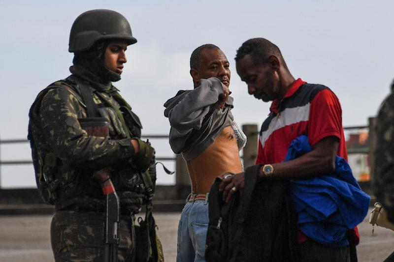 A soldier inspects a man's rucksack during a pre-dawn crackdown on criminal gangs in Rio de Janeiro, Brazil, on August 5, 2017 (AFP Photo/Apu Gomes)