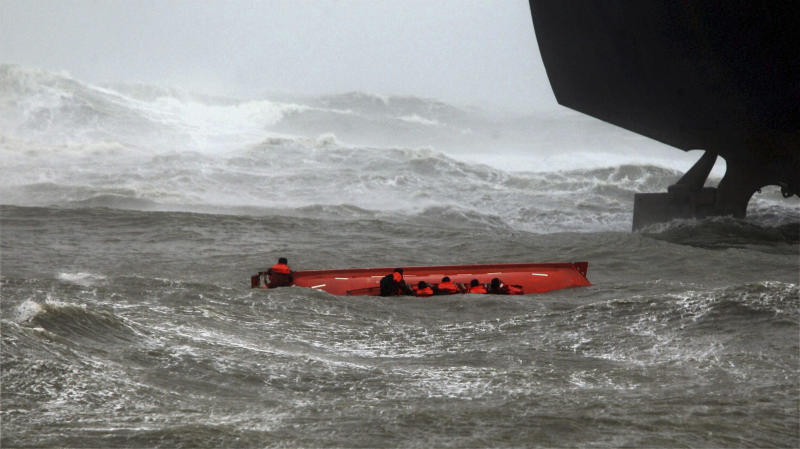 Sailors try to hold on to their up-turned lifeboat, as sailors, not pictured, throw lines to them from the ship above, after the lifeboat capsized when Indian ship Pratibha Cauvery, right, ran aground, due to strong winds in the Bay of Bengal coast in Chennai, India, Wednesday, Oct. 31, 2012. More than 100,000 people were evacuated from their homes Wednesday as a tropical storm hit southern India from the Bay of Bengal, officials said.(AP Photo) INDIA OUT