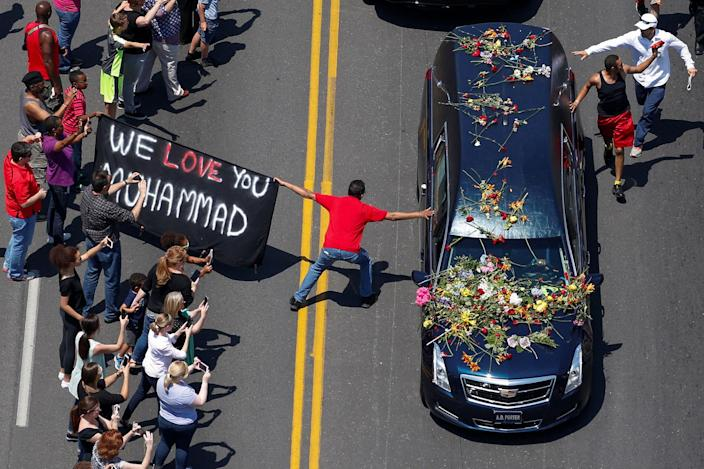 "<p>JUN. 10, 2016 — A banner stating ""We Love You Muhammad"" is displayed as well-wishers touch the hearse carrying the body of the late boxing champion Muhammad Ali during his funeral procession through Louisville, Kentucky. (Adrees Latif/Reuters) </p>"