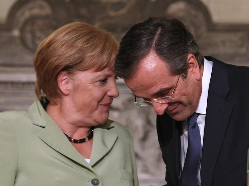 FILE - In this Oct. 9, 2012 file picture Greece's Prime Minister Antonis Samaras, right, and Germany's Chancellor Angela Merkel speak after their statements to the media at the Maximos mansion in Athens. German Chancellor Angela Merkel's upcoming re-election battle is shaping Europe's response to bailing out debt-ridden Greece.The strategy: do just enough to keep Greece afloat but spare German voters _ for now _ the news that their money will be required to get the Greeks back on their feet.  The deal reached Tuesday by the 17 nations that use the euro is a patchwork of measures to plug new shortfalls in Greece's budget and trim its debt load over the coming years. But it stopped short of forgiving some of the country's debt held by its eurozone creditors _ known euphemistically as a so-called haircut. (AP Photo/Thanassis Stavrakis, Pool, File)