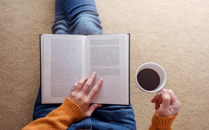 A woman reads a book and holds a mug of coffee - Getty Images Contributor/Sirinapa Wannapat / EyeEm