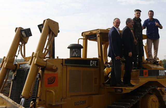 (L-R) Rio 2016 Olympic Games Organising Committee President Carlos Arthur Nuzman, Brazil's Sports Minister Aldo Rebelo, Brazil's Army General Enzo Martins Peri and Rio de Janeiro's Mayor Eduardo Paes pose on a tractor during the launch ceremony of the construction works of Deodoro Sports Complex for the Rio 2016 Olympic Games, in Rio de Janeiro July 3, 2014. REUTERS/Ricardo Moraes (BRAZIL - Tags: SPORT OLYMPICS POLITICS BUSINESS CONSTRUCTION)