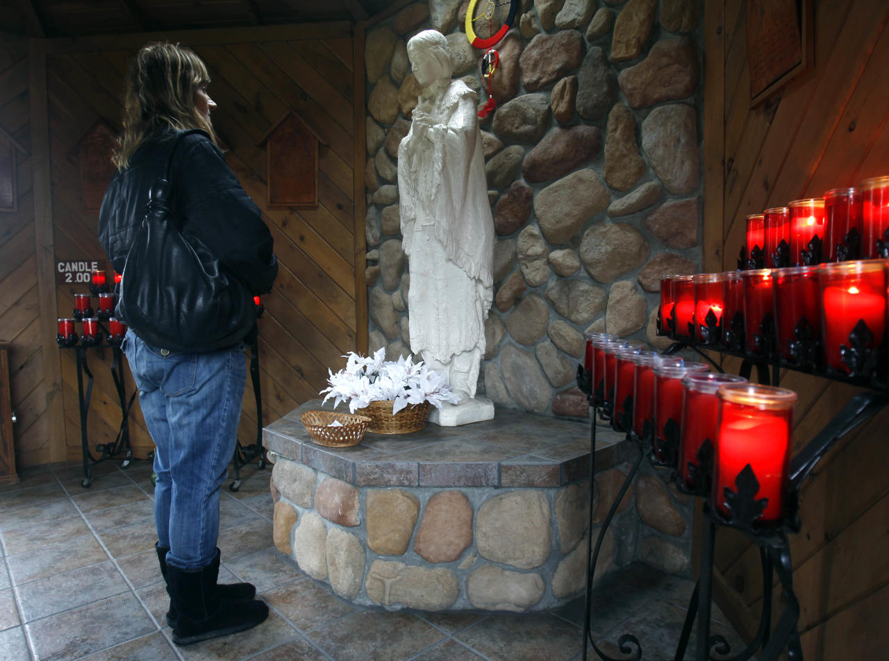 in a Wednesday, Dec. 21, 2011 photo, Phyllis Tessitore of Amsterdam, N.Y., says a prayer in front of a statue of the the Blessed Kateri Tekakwitha at the National Kateri Shrine and Indian Museum in Fonda, N.Y. Tekakwitha, who will be canonized next year, was a Native American baptized in 1676 in the Mohawk Valley. She fled to a mission in Canada after being scorned and threatened in her home village near what is now the village of Fonda. (AP Photo/Mike Groll)