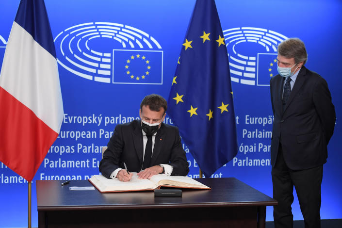 French President Emmanuel Macron signs a book next to European Parliament President David Sassoli before taking part in the Europe Day and the Conference on the Future of Europe, Sunday, May 9, 2021 at the European Parliament in Strasbourg, eastern France. (Frederick Florin, Pool via AP)