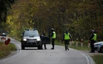 Polish police officers examine vehicles at a checkpoint on entry to the prohibited state of emergency zone, created to better manage an ongoing migrant crisis on the Belarusian-Polish border near Bialowieza