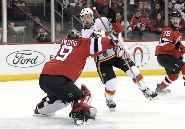 New Jersey Devils goaltender Mackenzie Blackwood (29) makes a save as he is screened by Calgary Flames left wing Andrew Mangiapane during the first period of an NHL hockey game Wednesday, Feb. 27, 2019, in Newark, N.J. (AP Photo/Bill Kostroun)