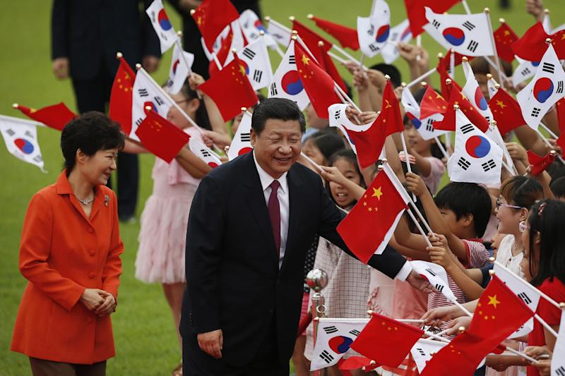 Chinese President Xi Jinping (C) and South Korean President Park Geun-hye (L) greet children waving the two national flags during a welcoming ceremony at the presidential Blue House in Seoul on July 3, 2014