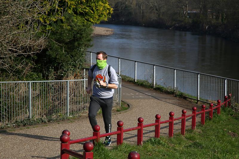 "A jogger exercises in a park in Cardiff, south Wales on the morning on March 24, 2020 after Britain's government ordered a lockdown to slow the spread of the novel coronavirus. - Britain was under lockdown March 24, its population joining around 1.7 billion people around the globe ordered to stay indoors to curb the ""accelerating"" spread of the coronavirus. (Photo by GEOFF CADDICK / AFP) (Photo by GEOFF CADDICK/AFP via Getty Images)"