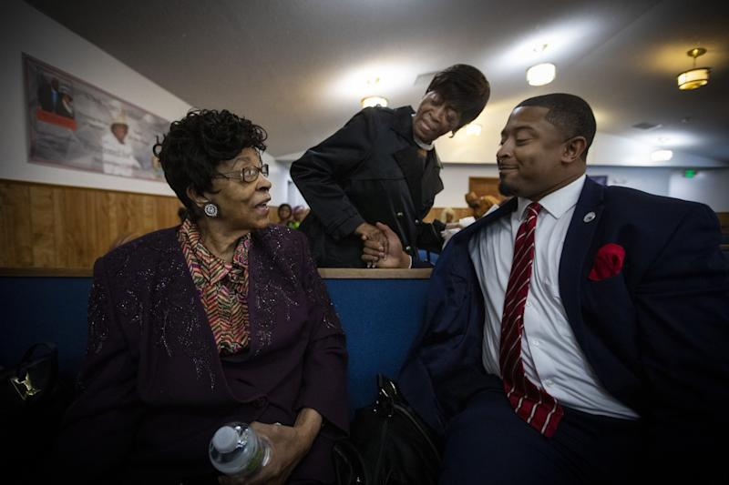State Rep. James Coleman, right, speaks with churchgoers in Denver.