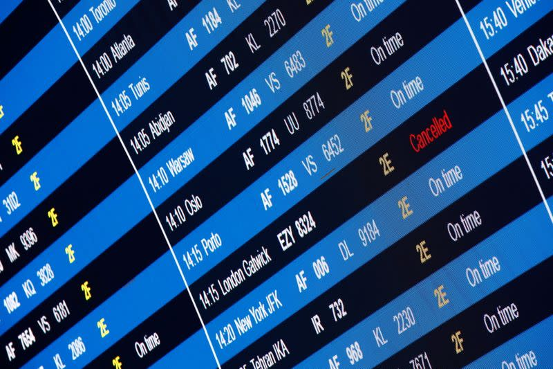 A departures board shows a cancelled flight from Paris to London Gatwick at Paris Charles de Gaulle airport