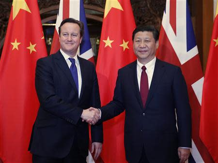 China's President Xi Jinping (R) shakes hands with Britain's Prime Minister David Cameron in front of Chinese and British flags during a meeting at Diaoyutai State Guesthouse in Beijing December 2, 2013. REUTERS/Ju Peng/Xinhua