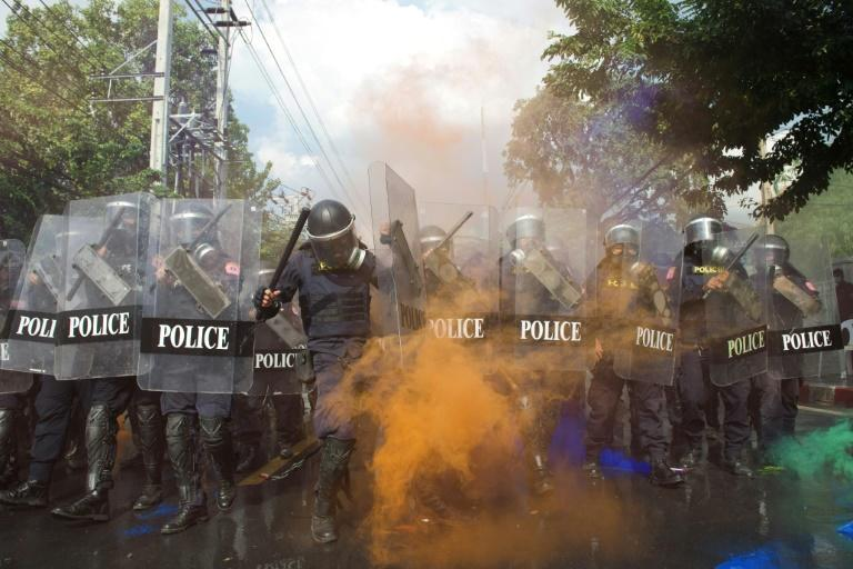 Orange smoke from a smoke grenade engulfs a line of police attempting to disperse pro-democracy protesters during an anti-government rally near the Thai Parliament in Bangkok on November 17, 2020