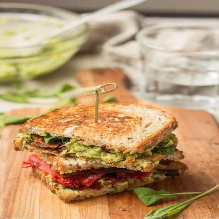 A thick toasted sandwich with avocado and other ingredients