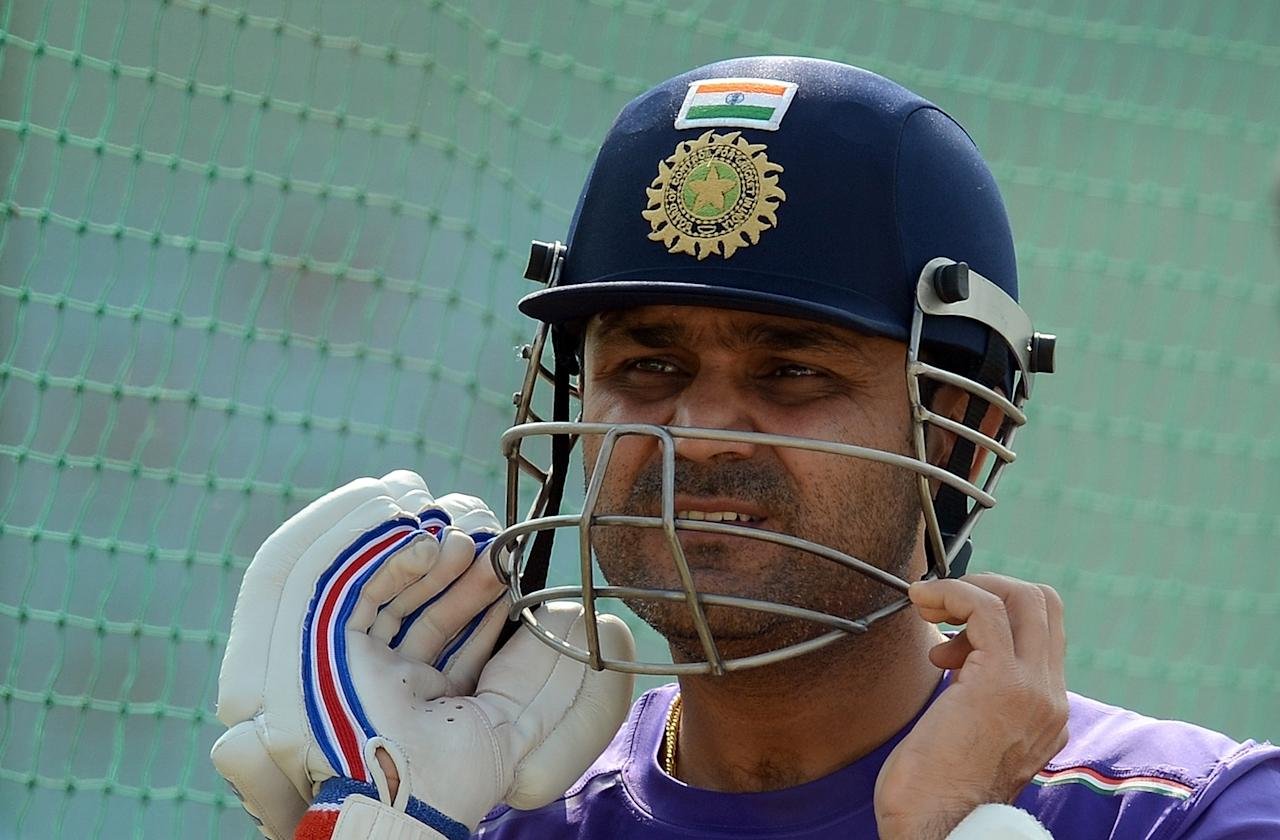 Indian cricketer Virender Sehwag wears his helmet as he prepares to bat in the nets during a training session at The Sardar Patel Stadium at Motera in Ahmedabad on November 14, 2012. India plays their first test cricket match against England from November 15 in Ahmedabad. AFP PHOTO/ PUNIT PARANJPE