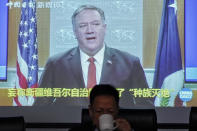 FILE - In this Feb. 1, 2021, file photo, Xu Guixiang, a spokesperson for Xinjiang's Communist Party, drinks as a screen showing a footage of former U.S. Secretary of State Mike Pompeo, during a press conference related to Xinjiang issues at the Ministry of Foreign Affairs office in Beijing. A human rights group appealed to the United Nations on Monday, April 19, 2021 to investigate allegations China's government is committing crimes against humanity in the Xinjiang region. (AP Photo/Andy Wong, File)